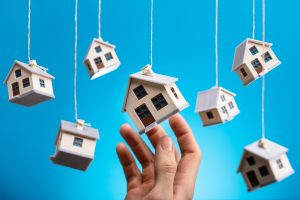 Person's Hand Holding Hanging Model House Against Blue Background