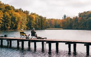 Couple fishing on dock at lake in autumn