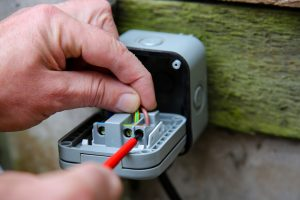 Man wiring an electric socket using an electrical screwdriver outdoor outside