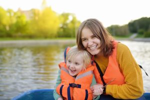 Mother with child in life vest on water